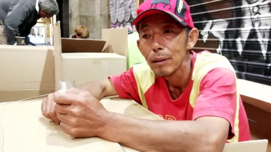 Pae, de 55 años, se acurruca entre cartones mientras espera que la lluvia no le vuelva a sorprender.