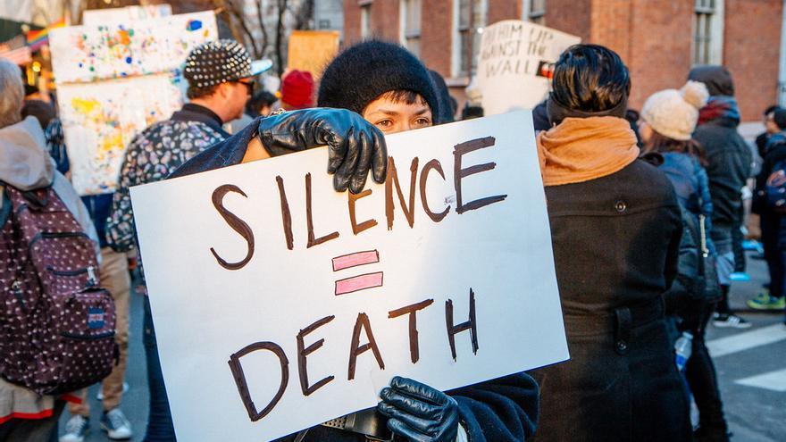 """""""El silencio equivale a la muerte"""" dice la pancarta alzada en una manifestación po-LGBTI frente al Stonewall Inn."""