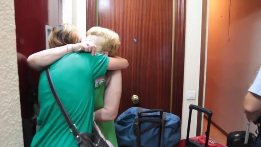 Irene, de espaldas, saca sus pertenencias de la casa de su madre el día del desahucio./ PAH Barcelona.