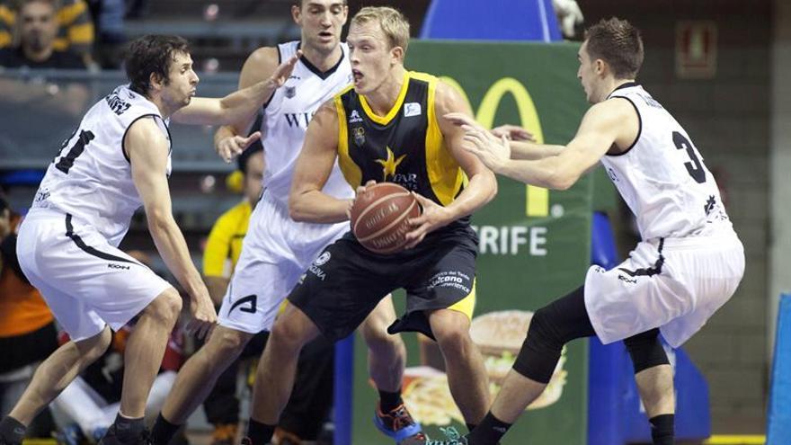 El jugador estadounidense del Iberostar Tenerife, Luke Sikma, ante la defensa de los jugadores del Bilbao Basket. EFE/Ramón de la Rocha.