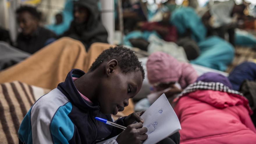 Uno de los niños rescatados el pasado 21 de diciembre dibujando con un bolígrafo y un papel que le dio el capitán del barco / Olmo Calvo