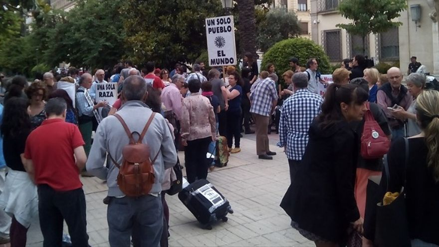 """Una mujer porta entre el público una pancarta con el mensaje """"Un solo pueblo, el mundo"""" / AECOS"""
