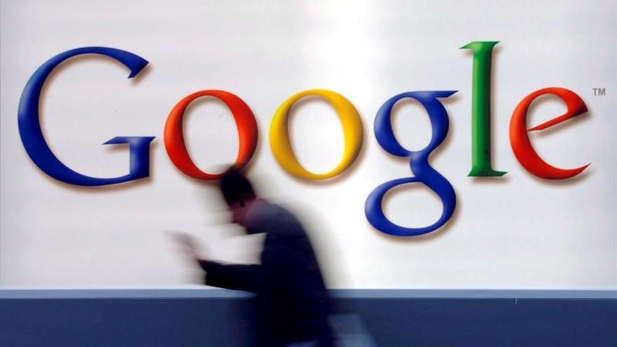 Un usuario mira su móvil frente al logo de Google.