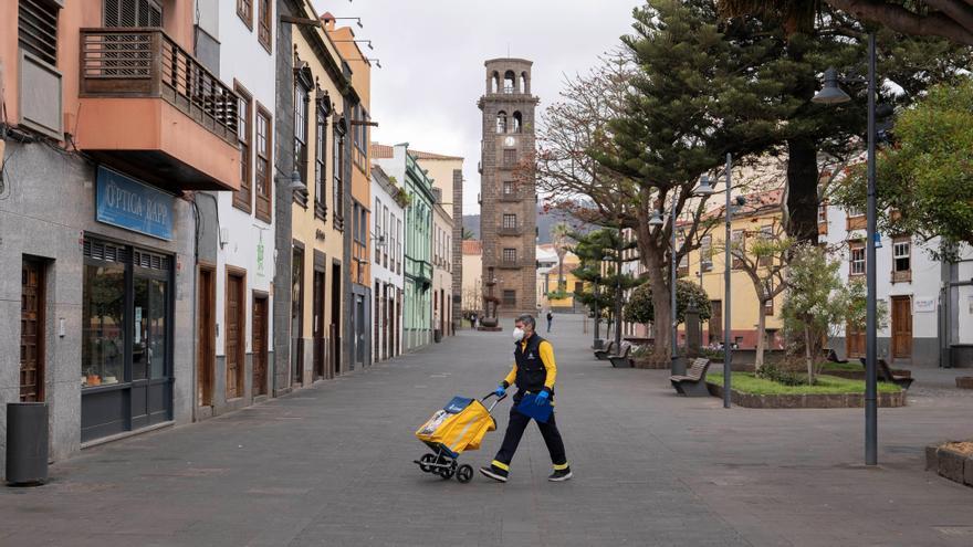 Un empleado de Correos realiza su trabajo con la torre de la iglesia de la Concepción de fondo en La Laguna durante el estado de alarma decretado para contener el coronavirus.