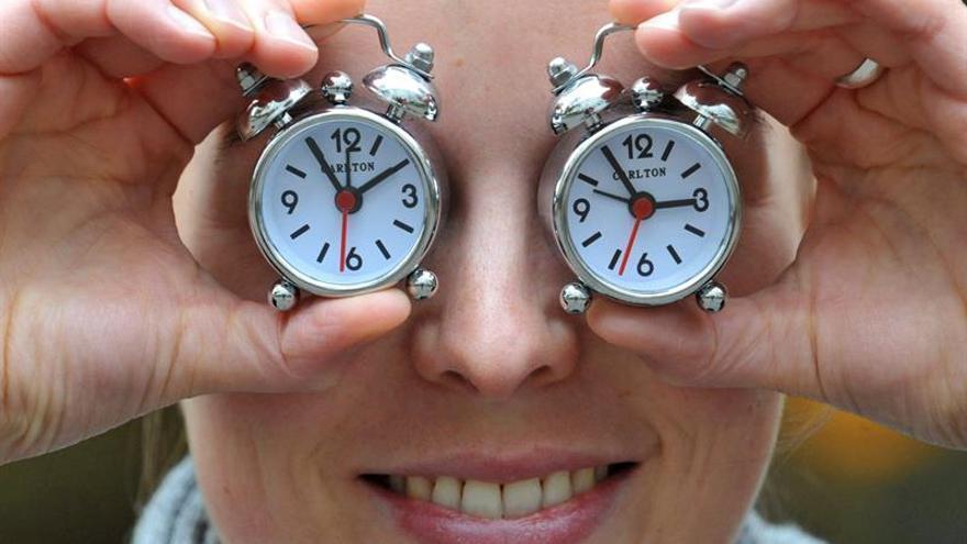 Una empleada del fabricante de relojes Carlton sostiene dos despertadores de la empresa para recordar sobre el cambio de hora.