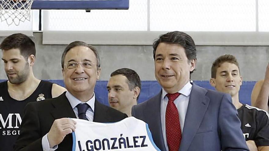 Ignacio González sostiene una camiseta del Real Madrid de baloncesto con su nombre, acompañado por el presidente del club, Florentino Pérez, en mayo de 2013 / EFE