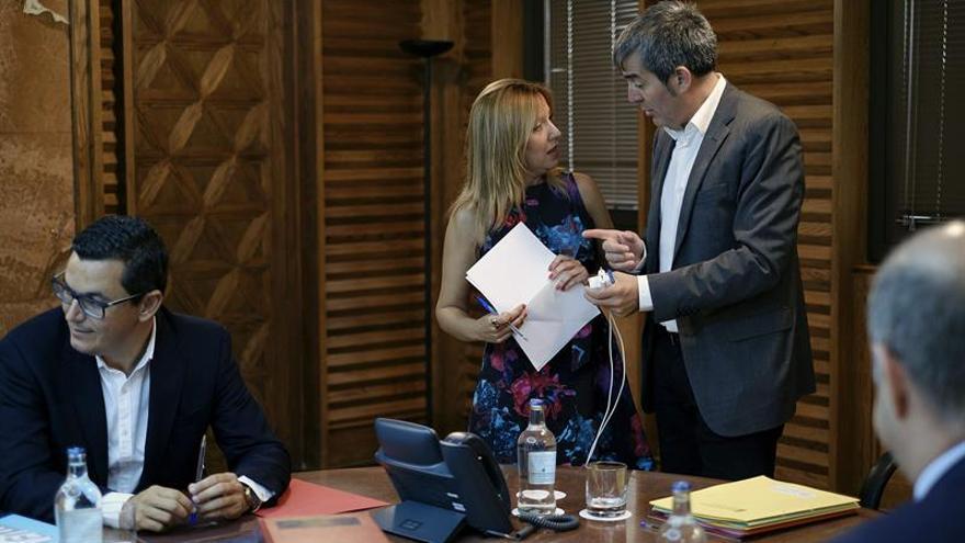 El presidente del ejecutivo regional, Fernando Clavijo (d) habla con la consejera de Hacienda, Rosa Dávila, al inicio de la reunión del Consejo de Gobierno.EFE/Ángel Medina G.