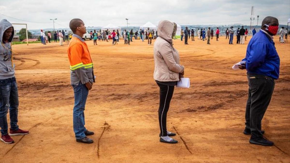 Varias personas hacen cola respetando la distancia de seguridad en Sudáfrica