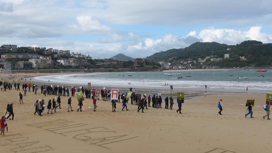 Decenas de personas realizan una cadena humana contra incineradora de Zubieta en la playa de La Concha de San Sebastián