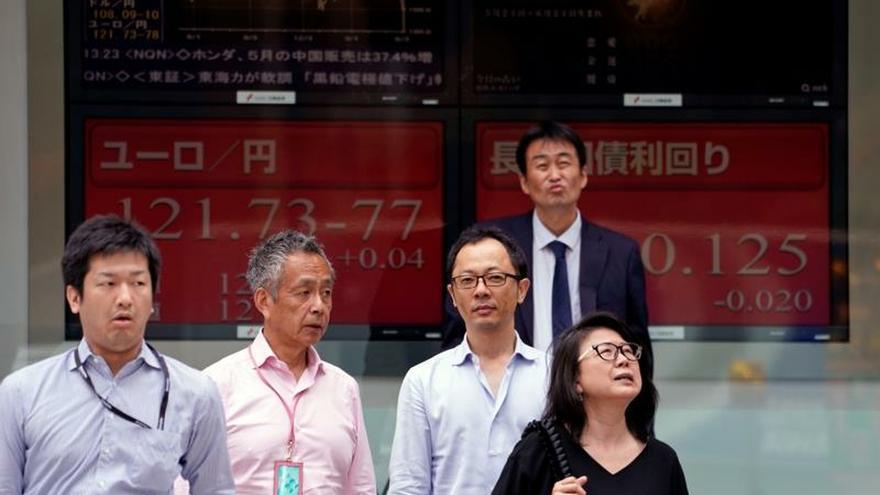 Peatones caminan junto a una pantalla que muestra información bursátil en Tokio (Japón).
