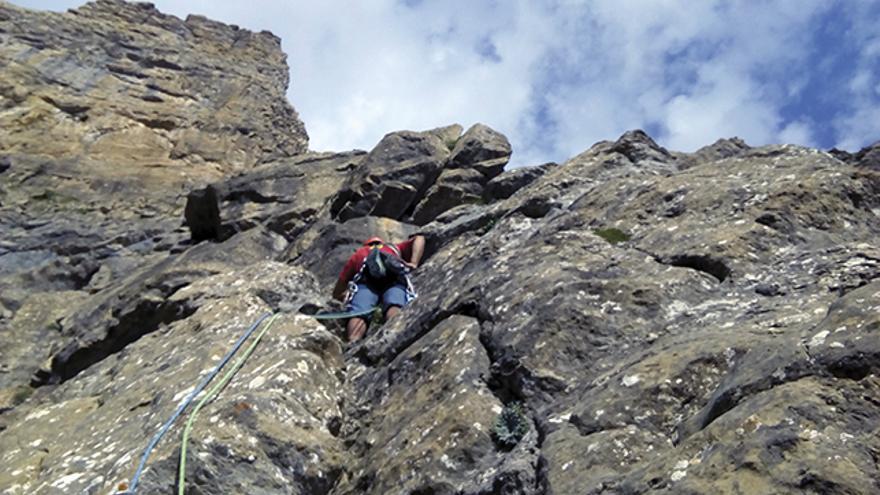 Miguel Larrosa liderando el primer largo entre placas y diedros con buena roca.