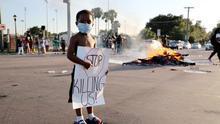 Protegido con mascarilla, un niño sujeta una pancarta en una calle cortada durante las protestas en Tampa, Florida