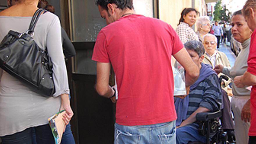 El vocal de una mesa electoral en Alcaravaneras saca a la calle una urna para que pueda votar una electora en silla de ruedas. (L.J.V)