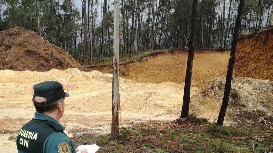 Un agente de la Guardia Civil inspeccionando el movimiento de tierras realizado en la mina romana de O Rosal (Pontevedra)