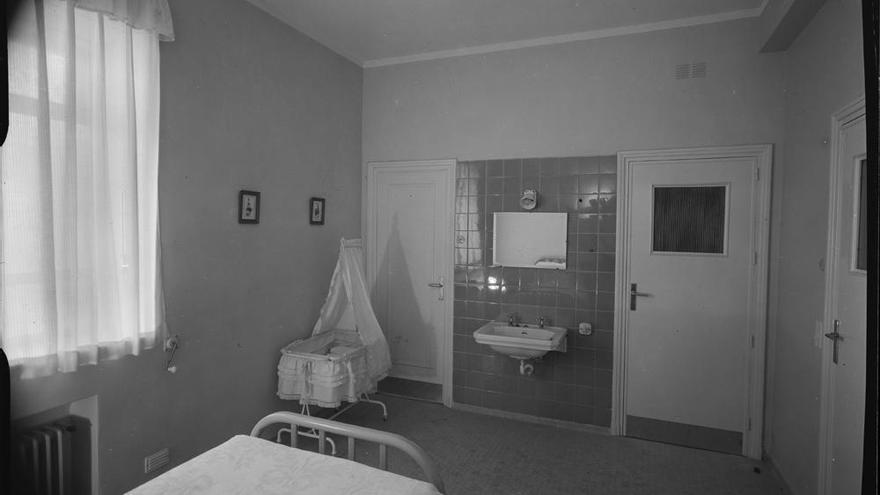Habitación de maternidad con cama, cuna y lavabo en la Residencia de la Seguridad Social Nuestra Señora del Perpetuo Socorro de Albacete