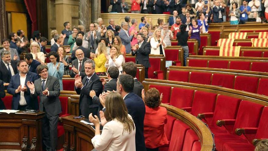 Los diputados del bloque independentista aplauden el resultado de la votación junto a los escaños de la oposición.