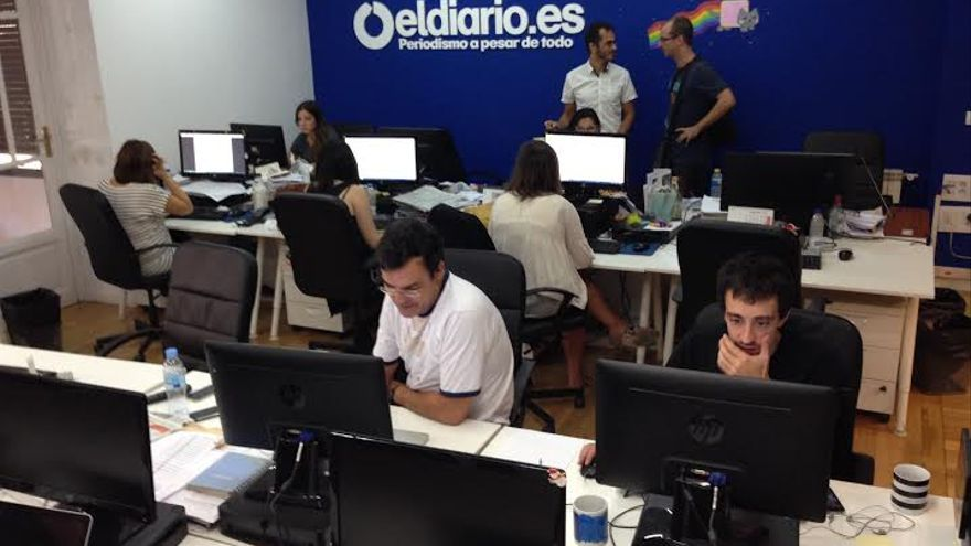 La redacción de eldiario.es con el nuevo logo en la pared.