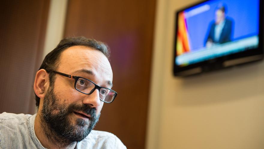 Benet Salellas habla mientras, al fondo, se ve en la televisión la comparencia de Artur Mas / SANDRA LÁZARO