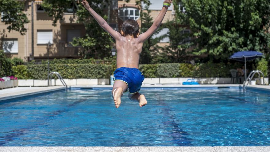 Un niño se lanza a una piscina.