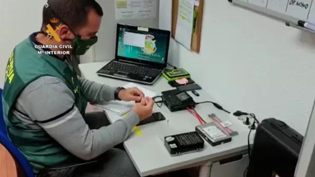 Agente de la Guardia Cilvil inspeccionando los dispositivos requisados al detenido