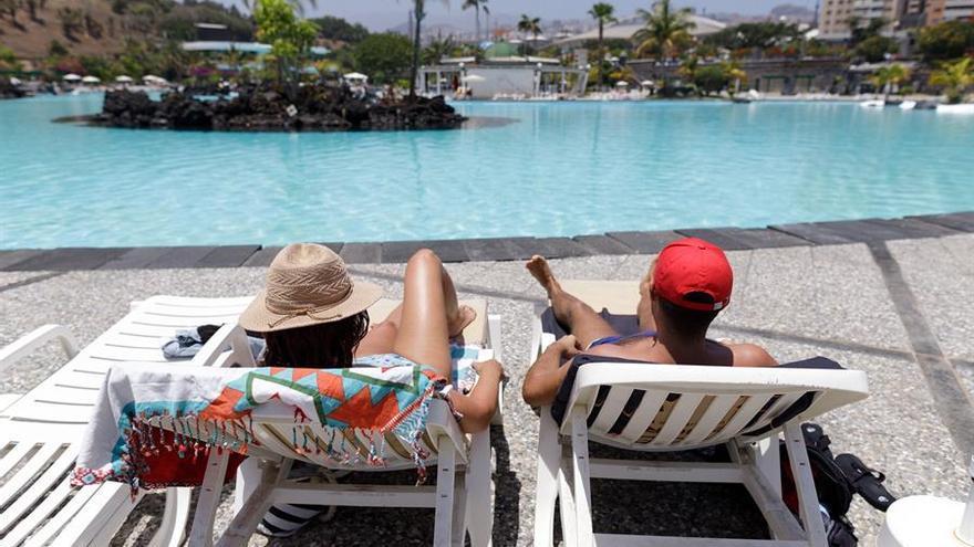 Una pareja toma el sol en el Parque Marítimo de Santa Cruz de Tenerife, que este martes abrió por primera vez sus puertas tras la declaración del estado de alarma.