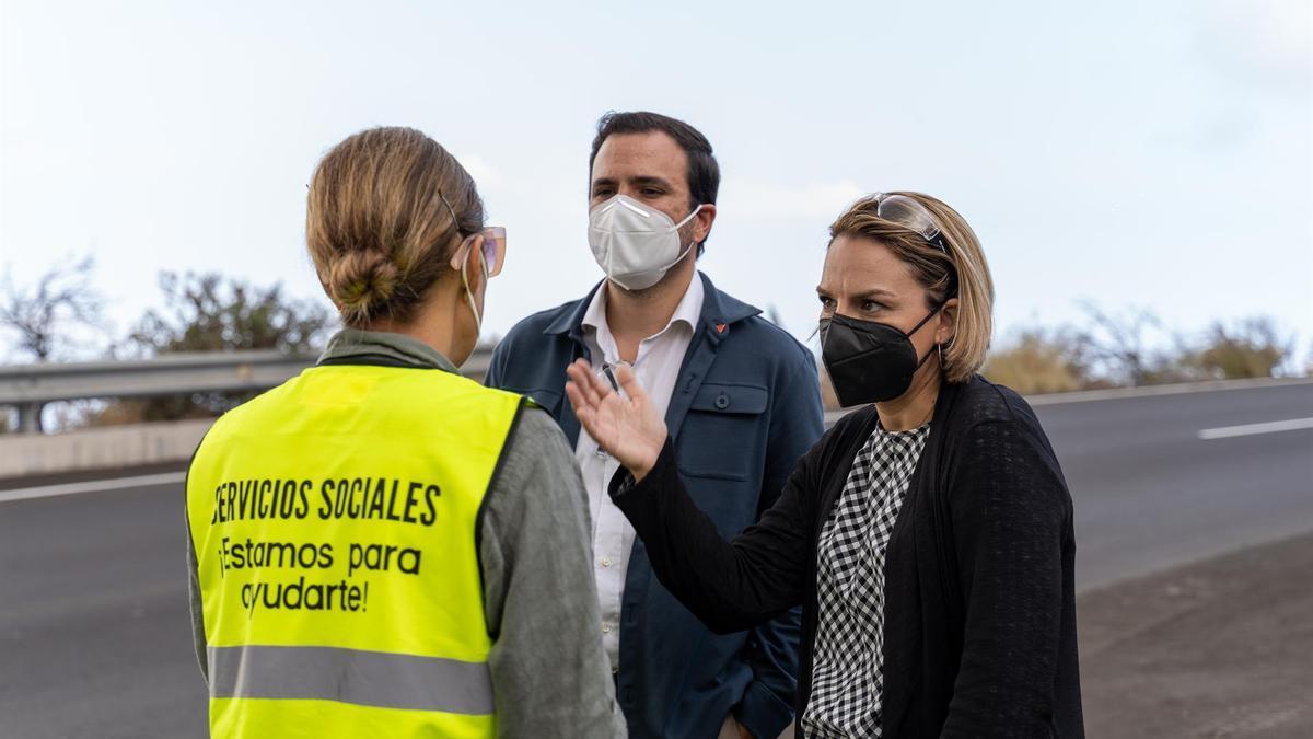 El ministro de Consumo, Alberto Garzón, y la consejera de Derechos Sociales del Gobierno de Canarias, Noemí Santana, conversan con una trabajadora de servicios sociales durante una visita al acuartelamiento de El Fuerte