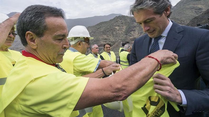 """Miembros del Foro Aldeano entregan una camiseta con el texto """"Salvar La Aldea ¡¡Carretera Ya!!"""", al ministro de Fomento, Iñigo Joaquín de la Serna. EFE/Ángel Medina G."""