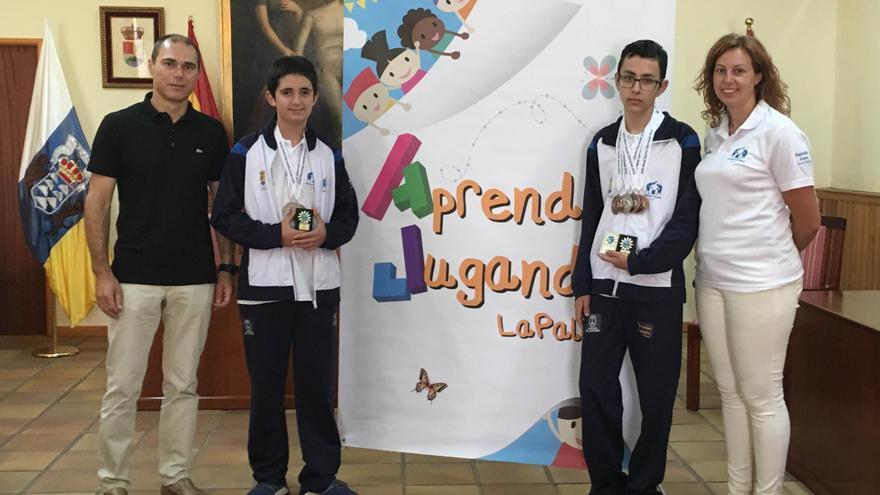 Los jóvenes Víctor Hernández Luis y Héctor Rodríguez Rodríguez, integrantes del equipo palmero que participó en las XX Olimpiadas de Deportes Mentales, junto con el alcalde de Mazo y la representante de la iniciativa.
