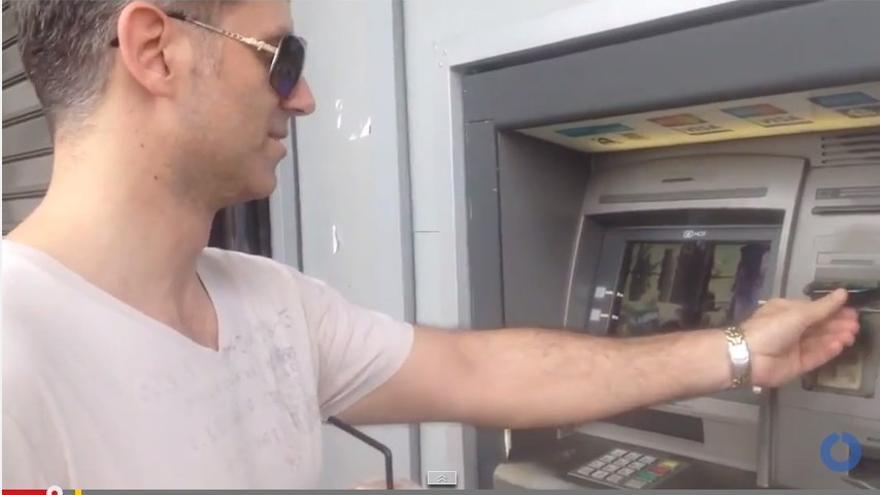 Ciudadano griego saca dinero de un cajero durante el corralito