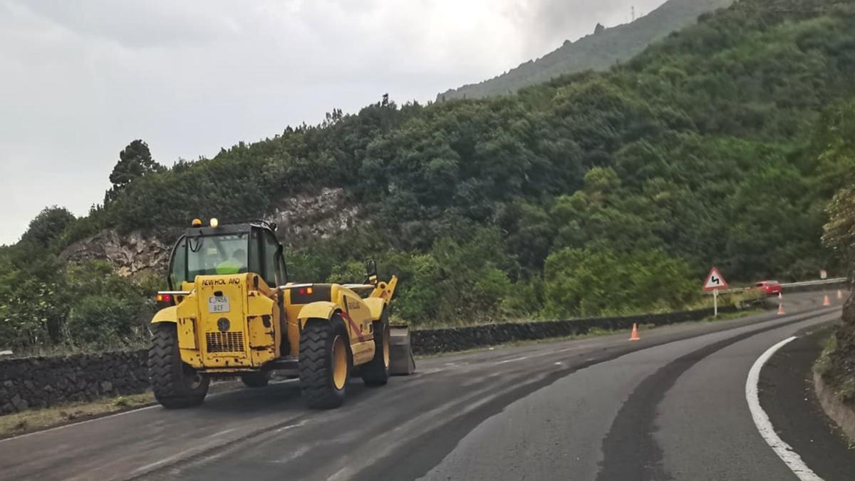 Una pala mecánica retira de una de las carreteras de La Palma la ceniza arrojada por el nuevo volcán.
