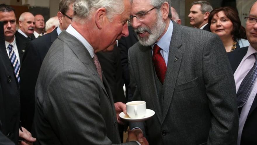Charles Windsor estrecha la mano de Gerry Adams mientras con la otra mano sostiene una taza.
