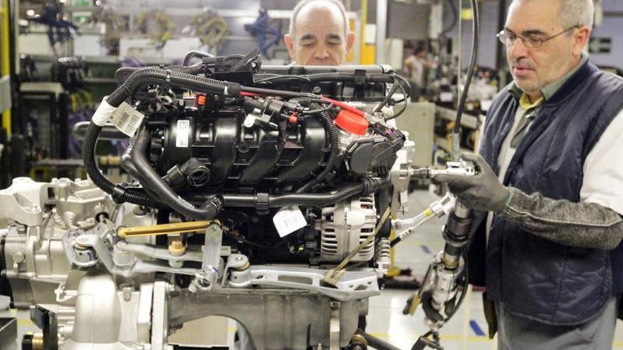 Trabajadores de la cadena de montaje de la factoría que GM España tiene en Figueruelas (Zaragoza), colocan piezas en un motor.