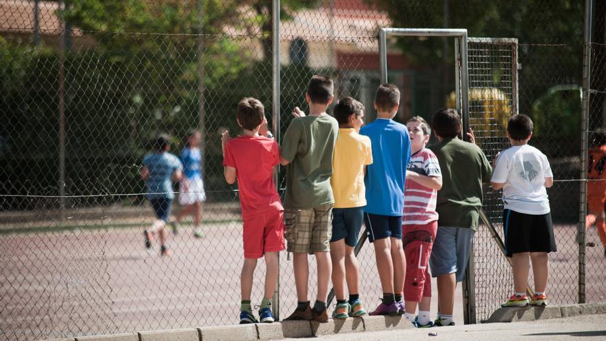 Un grupo de niños juega en el patio del colegio.