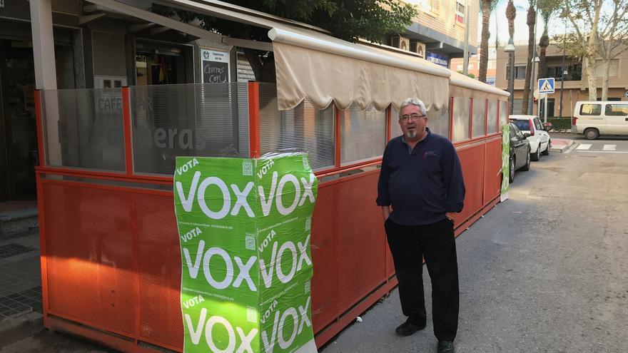 José Antonio Herrera posa junto a los carteles de VOX pegados en la terraza del bar que regenta junto a su socia, de nacionalidad búlgara.