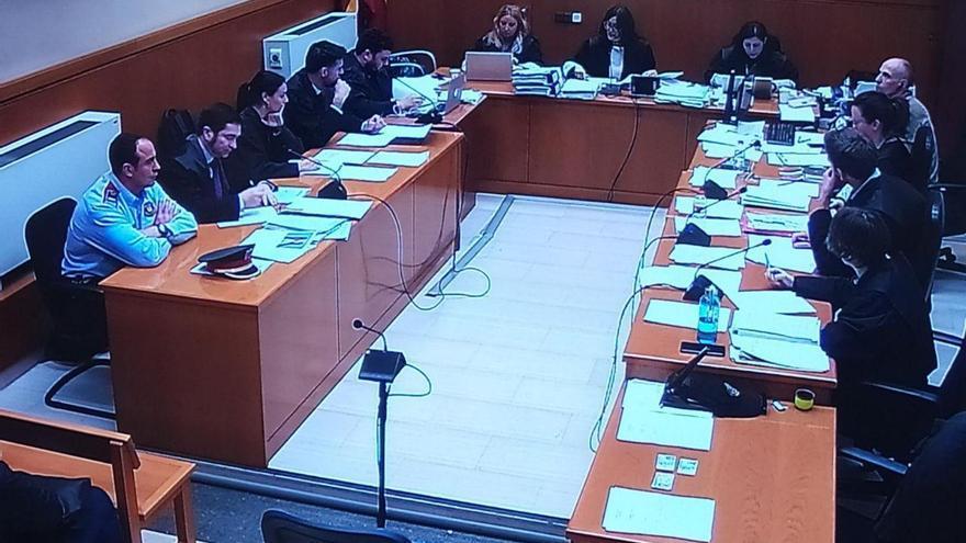 El subinspector Jordi A., sentado a la izquierda de su abogado y vestido de uniforme.