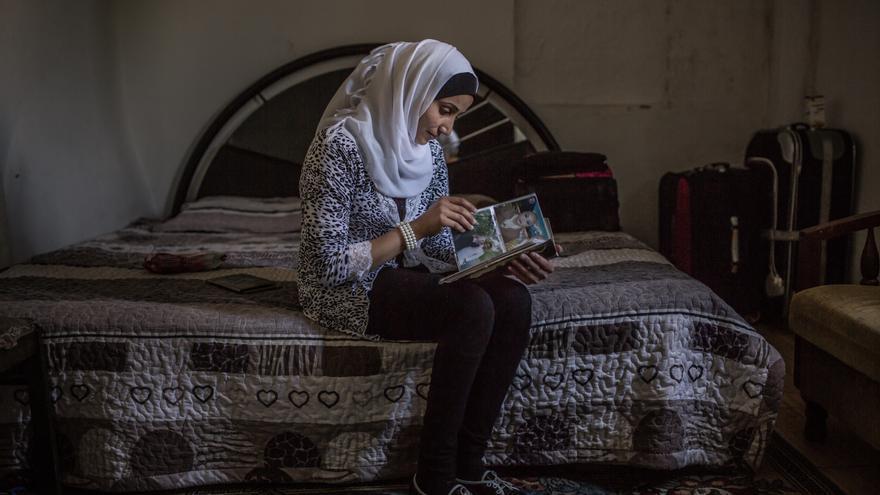 Foto: Fatem revisa las fotografías del albúm familiar, el único objeto que trajo consigo al huir de Siria. Fatem era docente de una escuela, los constantes bombardeos la forzaron a huir de su ciudad natal Raqqa en Siria con su esposo Khalil y su hijo menor Mohamed en 2013. Autor: Pablo Tosco / Oxfam Intermón