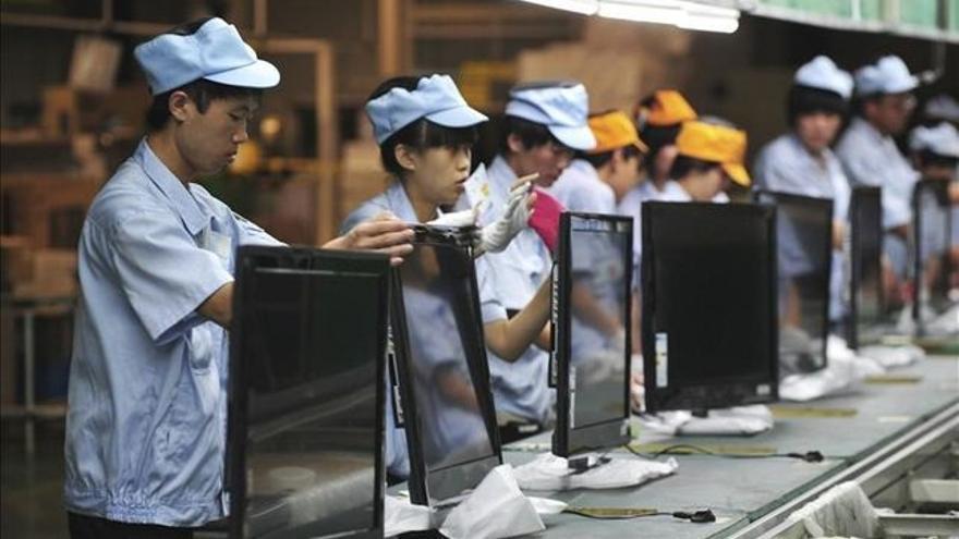 Trabajadores chinos montan televisores.