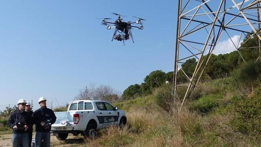 Operarios de Endesa pilotan un dron junto a una línea de conducción de electricidad.