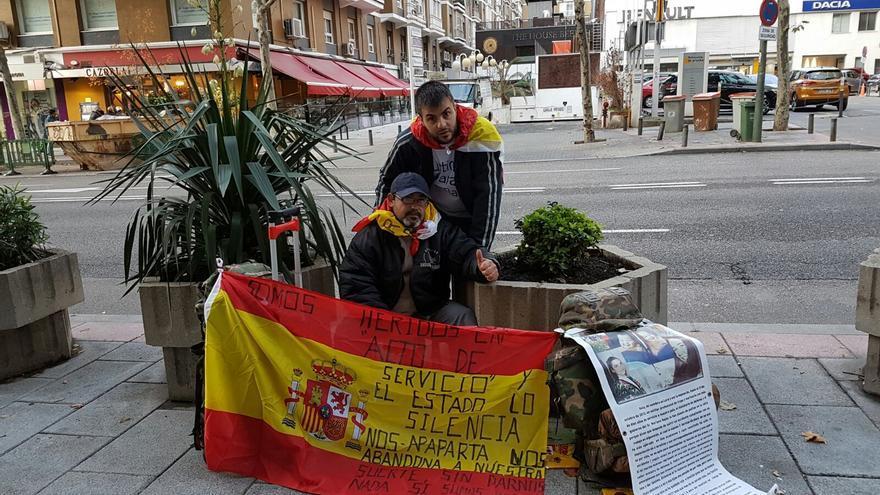 Andrés Merino (sentado) junto al exsoldado Iván Ramos protestando en Defensa