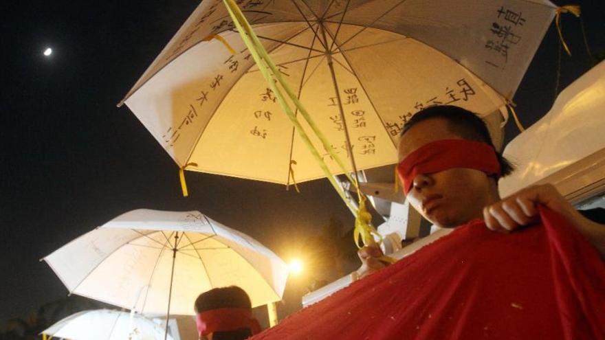 Manifestantes chinos se cubren la cara mientras protestan por la democracia en Liberty Square. Foto: Chiang Ying-ying/AP