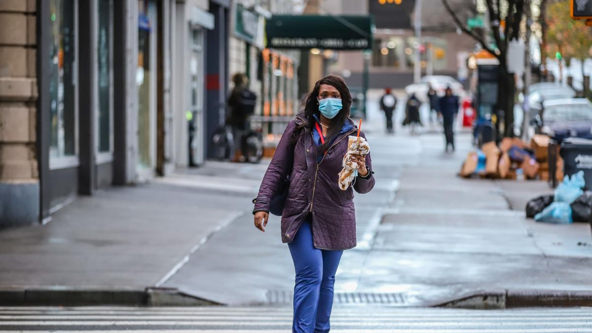 Una mujer pasea con mascarilla por Nueva York, Estados Unidos