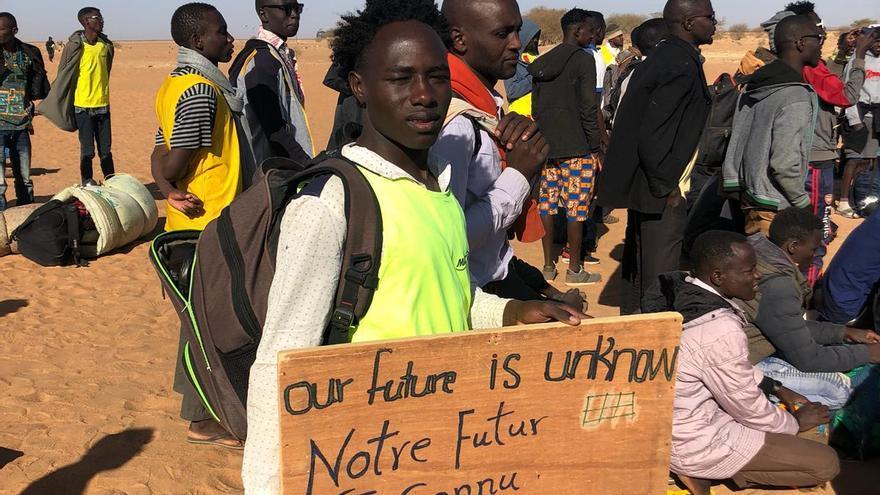 """Uno de los refugiados sostiene un cartel donde puede leerse """"Nuestro futuro es incierto"""" escrito en inglés y francés"""