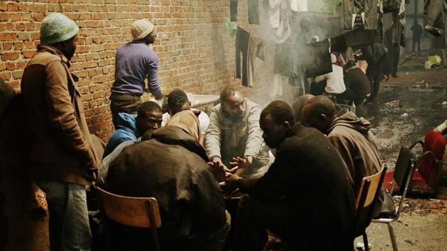 Un grupo de hombres se caliente en torno a un fuego en la Vandamme en Calais //FOTO: UNHCR /J. Pebrel