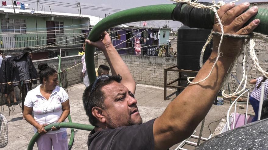 Marta Romo y su familia llenan los tanques de agua de su terrado con la manguera que les surte agua potable desde un camión cisterna de la Alcaldía de Iztapalapa, que puede tardar dos semanas en distribuirles.