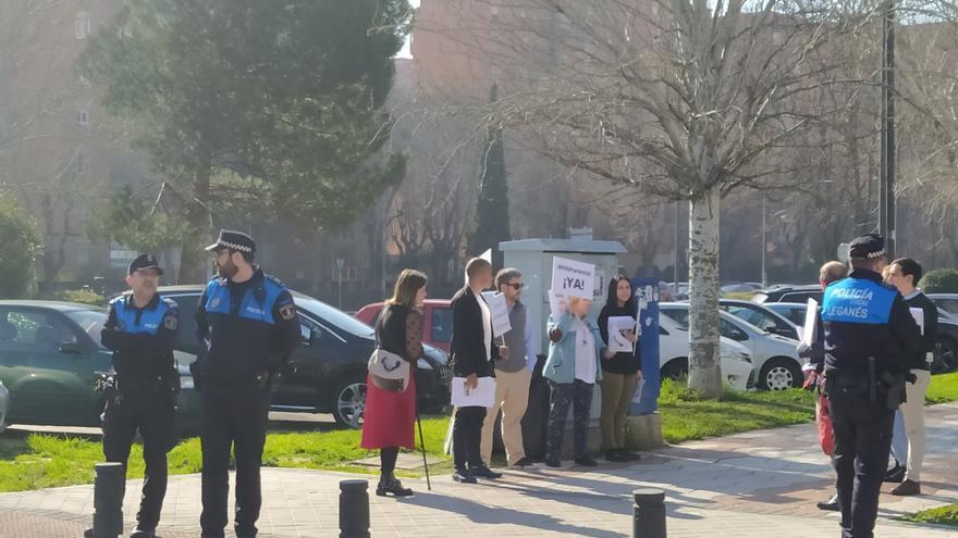 Varios miembros de Hazte Oír repartiendo sus folletos a unos metros del colegio ante la mirada de los agentes. / SPM