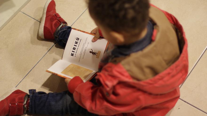 Un niño observa el libro 'Kirukú y el fetiche extraviado'