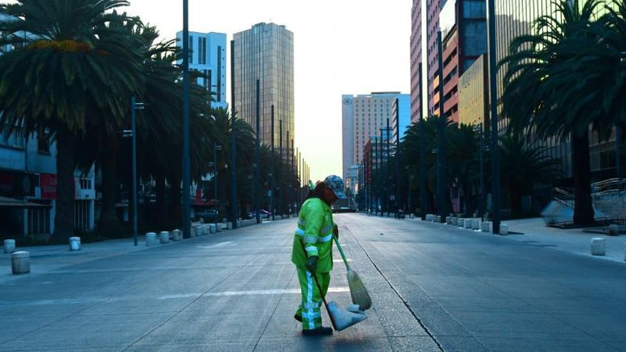 Un trabajador limpia este martes una avenida vacía un día después del decreto de emergencia sanitaria por parte del Gobierno de Andrés Manuel López Obrador, en Ciudad de México (México).