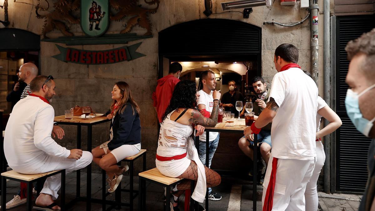 Un grupo de personas almuerza en una bar de la calle Estafeta este martes, 6 de julio, cuando debería lanzarse el tradicional chupinazo.   EFE/Jesús Diges