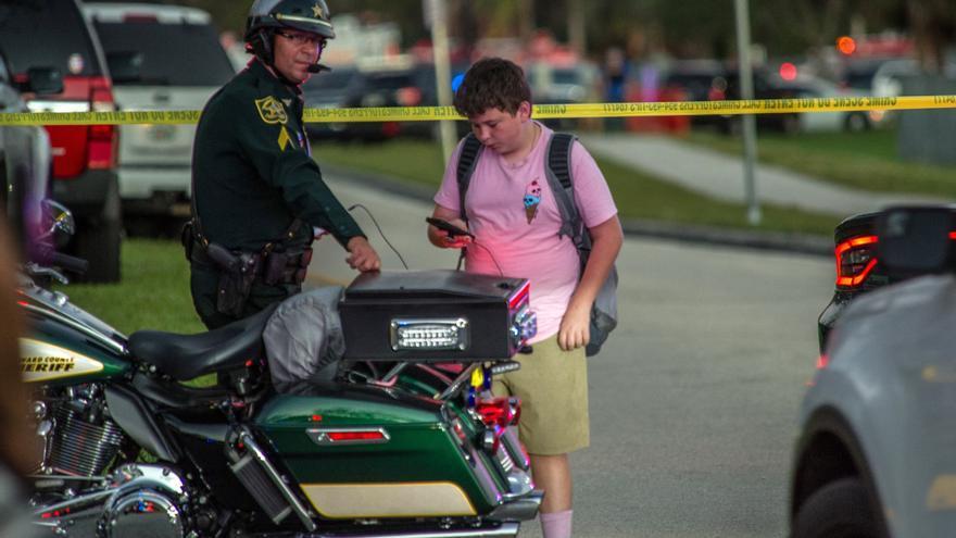 Un estudiante observa su teléfono móvil junto a un policía tras el tiroteo en la escuela secundaria Marjory Stoneman Douglas de la ciudad de Parkland