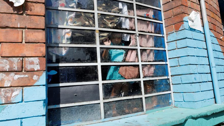 Una niña migrante venezolana mira desde la ventana del alojamiento donde se encuentra confinada este 27 de marzo en Bogotá, Colombia